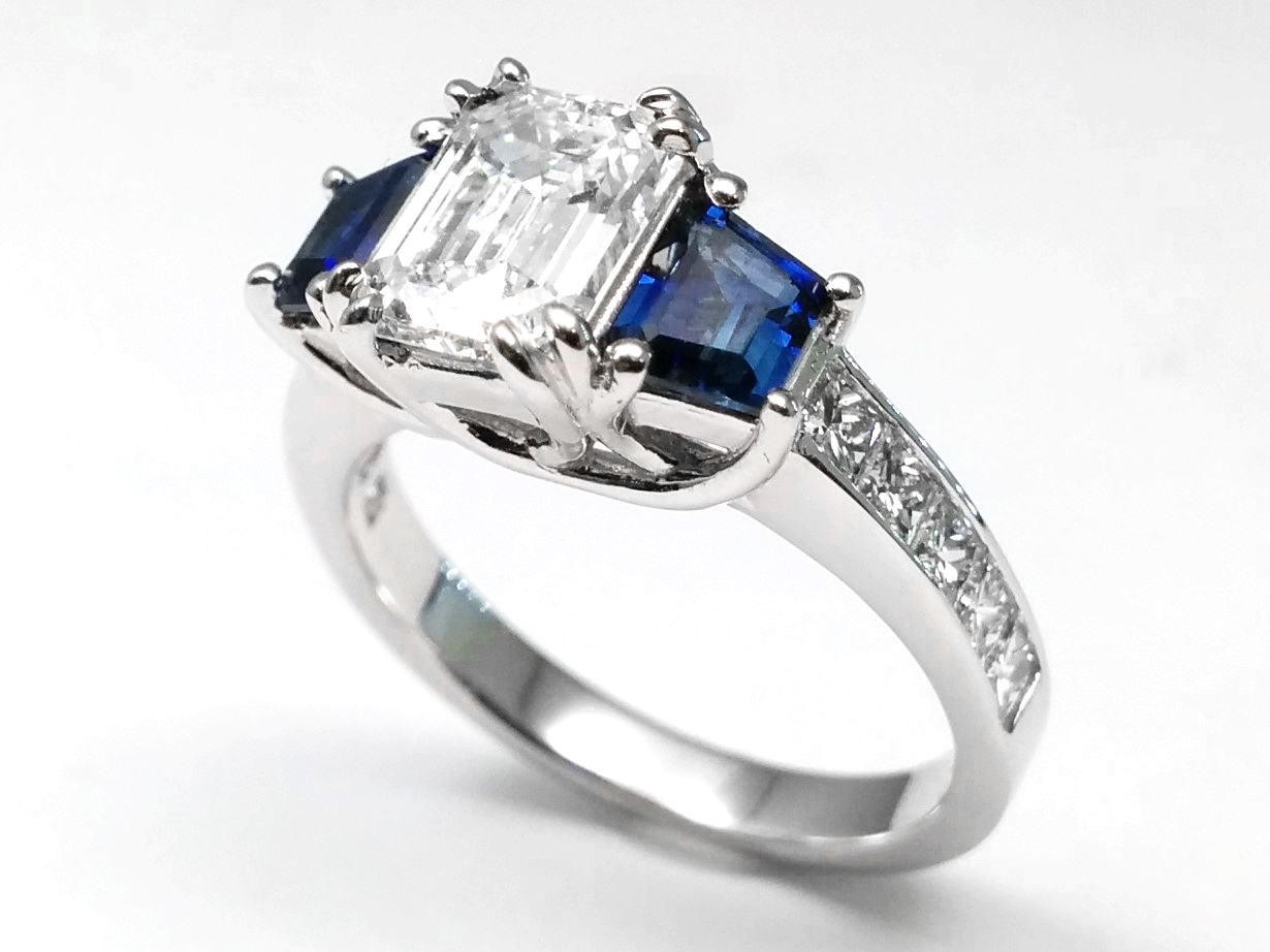 Emerald Cut Diamond With Princess Cut Diamonds & Trapezoid Cut Blue Sapphires